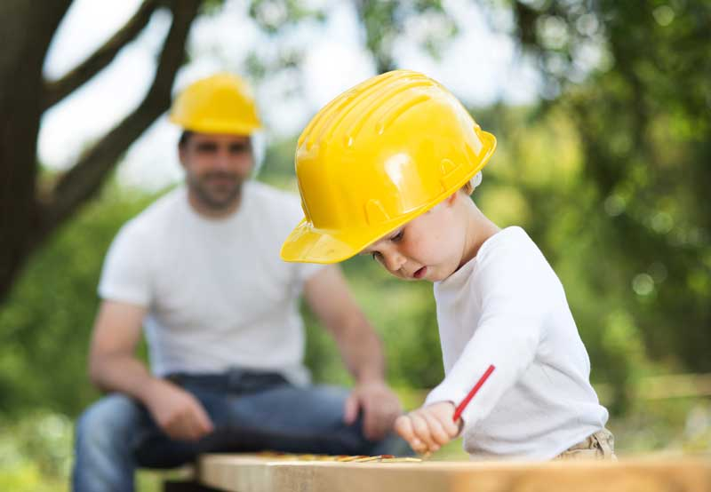 a young boy helping his dad with construction