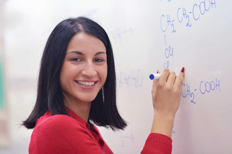 A girl writing formulas on a board